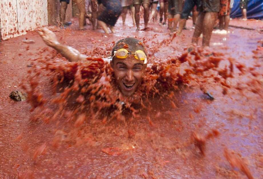 """A reveler dives on a street covered with squashed tomatoes during the """"Tomatina"""" fight in Bunol, near Valencia, on August 31, 2011. Tens of thousands of revellers splattered each other with 120 tonnes of squashed tomatoes in a gigantic annual food fight known as the Tomatina. The streets ran red with slippery juice as nearly 40,000 people, many stripped to the waist and drunk with sangria, pelted each other in the Plaza Mayor square and nearby streets of Bunol, eastern Spain. AFP PHOTO/ GERMAN GARCIA (Photo credit should read German Garcia/AFP/Getty Images) Photo: German Garcia, AFP/Getty Images"""