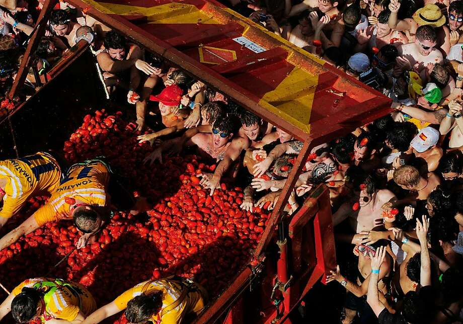 BUNOL, SPAIN - AUGUST 31:  A truck tips tomatos onto revellers during the annual tomatina festival on August 31, 2011 in Bunol, Spain. An estimated 35,000 people threw 120 tons of ripe tomatoes in the world's biggest tomato fight held annually in this Spanish Mediterranean town.  (Photo by Denis Doyle/Getty Images) Photo: Denis Doyle, Getty Images