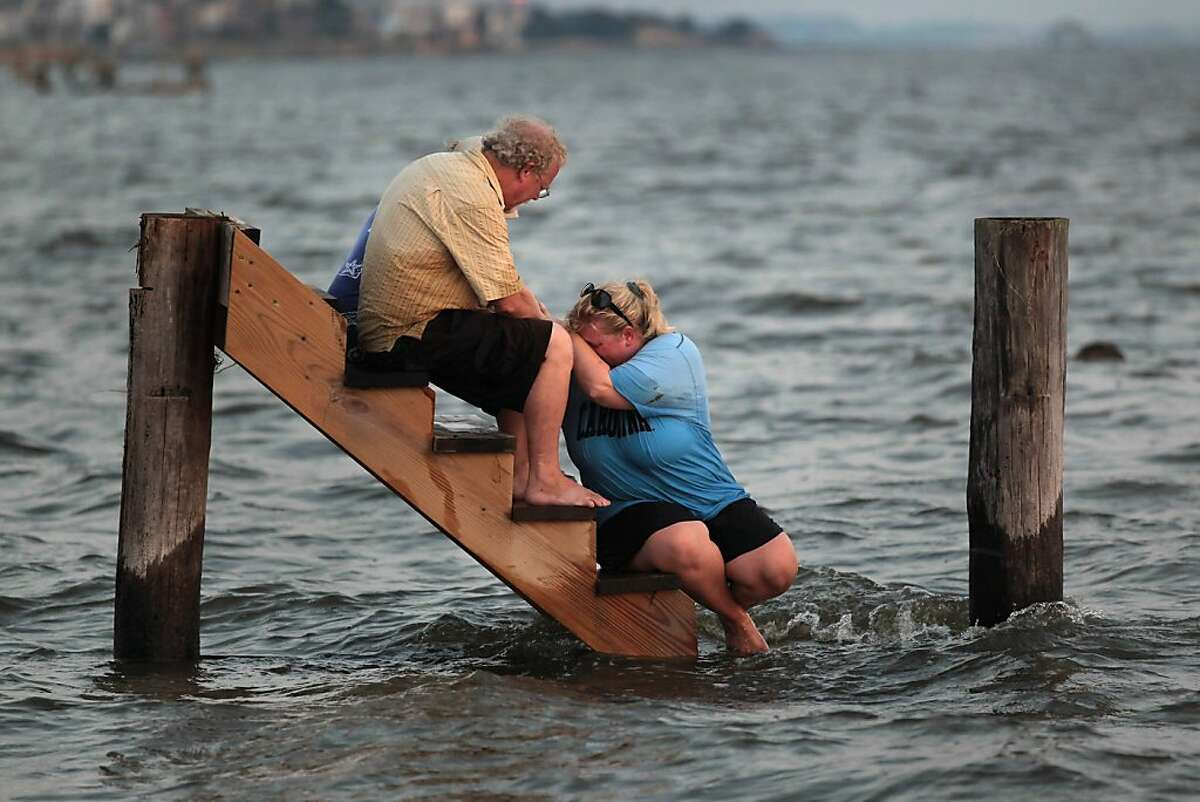 NAGS HEAD, NC - AUGUST 28: Billy Stinson (L) comforts his daughter Erin Stinson as they sit on the steps where their cottage once stood August 28, 2011 in Nags Head, North Carolina. The cottage, built in 1903 and destroyed yesterday by Hurricane Irene, was one of the first vacation cottages built on Albemarle Sound in Nags Head. Stinson has owned the home, which is listed in the National Register of Historic Places, since 1963.