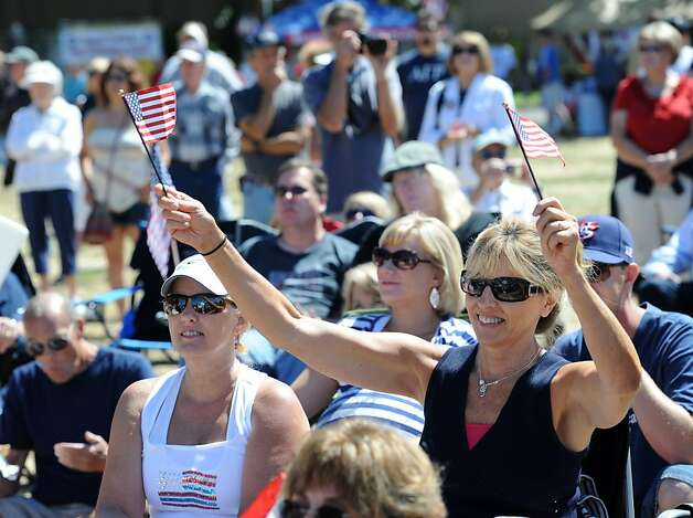 Heather Helmer raises flags during a song at the Napa Valley Expo during the Tea Party Express launch on August 27, 2011. Photo: Susana Bates, Special To The Chronicle
