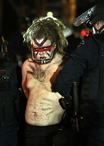 Los Angeles police officers arrest an Occupy Los Angeles protester at the encampment at the Losd Angeles city hall on Wednesday, Nov. 30, 2011. Police in Los Angeles and Philadelphia stormed Occupy Wall Street encampments in both cities Wednesday, demanding protestors leave demonstration sites.  (AP Photo/Mark Boster/Pool) Photo: Mark Boster, AP
