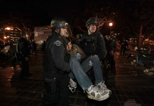 A frowning protester is arrested as Los Angeles police officers dismantle the Occupy LA encampment outside City Hall in Los Angeles November 30, 2011. The nearly two-month-old encampment is among the oldest and largest on the West Coast aligned with the Occupy Wall Street demonstrations protesting economic inequality in the country and the excesses of the U.S. financial system.  (AP Photo/Lucy Nicholson/Pool) Photo: Lucy Nicholson, AP