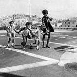 Three San Francisco kindergarten students cross the street on their first day of school. Sept. 17, 1971.