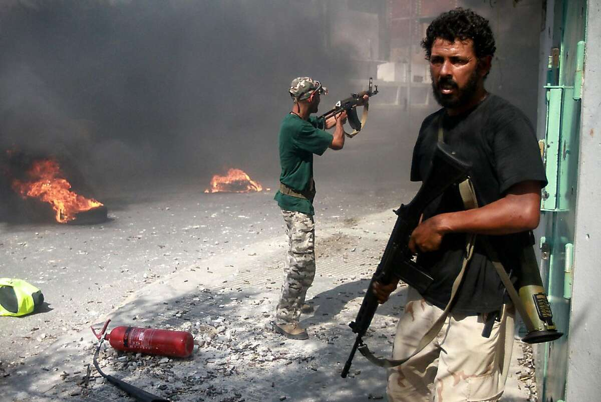 Libyan rebel fighters fire at regime forces during the battle for the control of Zawiya after setting tyres on fire to make smoke and take cover from snipers on August 19, 2011. Libyan rebels claimed to have taken two more key objectives in their advance on Tripoli, including the refinery town of Zawiya, as people scrambled to flee the increasingly isolated capital. AFP PHOTO/MARC HOFER (Photo credit should read MARC HOFER/AFP/Getty Images)