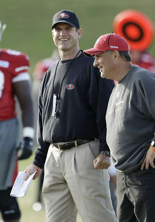 San Francisco 49ers coach Jim Harbaugh, left, and defensive coordinator Vic Fangio, right, smile during the NFL football team's training camp in Santa Clara, Calif., Thursday, Aug. 4, 2011. (AP Photo/Paul Sakuma) Photo: Paul Sakuma, AP