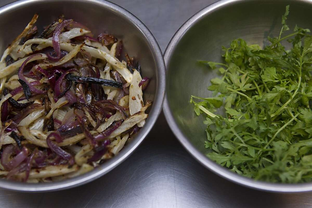 Roasted fennel with red onion and Neapolitan chiles, left and a bowl of peppercress are prepared before Executive Chef David Taylor adds them to a dish of roasted scallops at A16 restaurant in San Francisco Thursday, November 17, 2011. The scallop dish will be one of the many courses offered on the restaurant's Christmas Eve Feast of the 7 Fishes, prix-fixe menu.