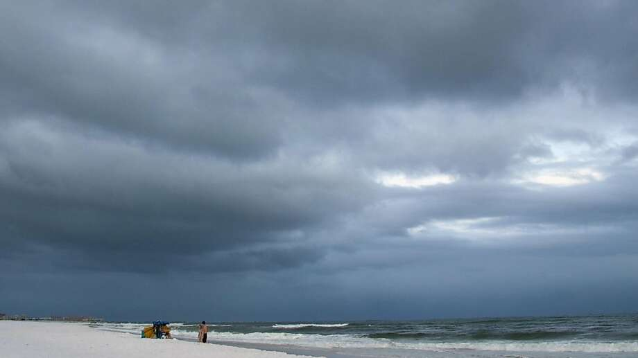 Beach goers stand beach side as dark clouds form in Fort Walton Beach, Fla., Sunday, Aug. 16, 2009, ahead Tropical Storm Claudette. (AP Photo/Mari Darr~Welch) Photo: Mari Darr~welch