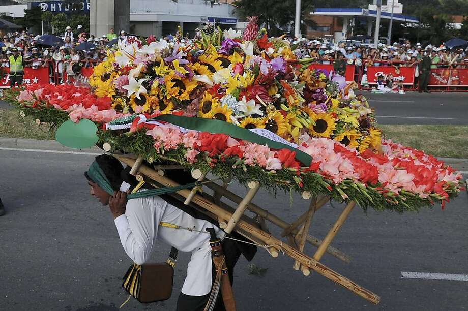 "A man parades carrying flowers during the annual Festival of Flowers in Medellin, Sunday, Aug. 7, 2011. This festival is one of the most important events of Medellin and it has been celebrated every year since 1957 with several activities such as the flower carriers parade called in Spanish ""Desfíle de Silleteros."" (AP Photo/Luis Benavides) Photo: Luis Benavides, AP"