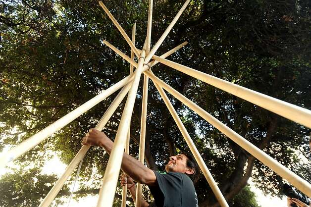 Protester Zachary RunningWolf erects a teepee near Oakland, Calif., City Hall on Tuesday, Nov. 29, 2011. After more than an hour of wrangling between his lawyer, police officers and city administrators, RunningWolf built the structure with the understanding that he'd remove it each night. Ran on: 11-30-2011 RunningWolf puts up the teepee after more than an hour of talks among his lawyer, police and city officials. Ran on: 11-30-2011 RunningWolf puts up the teepee after more than an hour of talks among his lawyer, police and city officials. Photo: Noah Berger, Special To The Chronicle