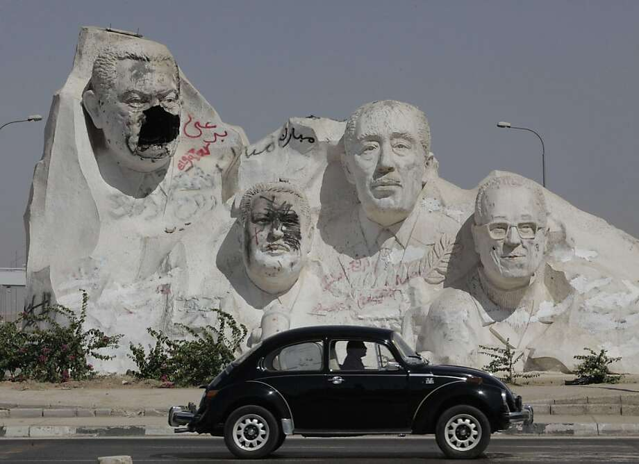 A Car Passes By Giant Statue Showing The Late Egyptian President Anwar Sadat Second