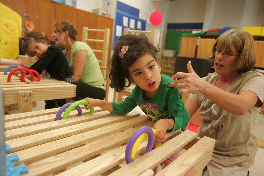 Conductive teachers Krisztina Bernstein, right, and Orsi Toth-Petho works with students Malia Sanchez, 5, and Gabriella Covello, 5, respectively, at the Conductive Learning Center of San Francisco in Glen Park. Conductive education is intended to help children with motor challenges (usually stemming from cerebral palsy, spina bifida, etc.) learn how to independently perform routine tasks and become mobile. Photo: Mathew Sumner, Special To The Chronicle