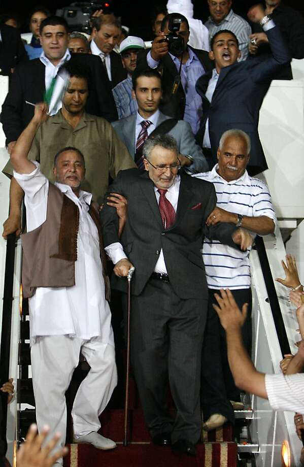 A handout picture obtained from Oya newspaper shows Libyans greeting freed Lockerbie bomber Abdelbaset Ali Mohmet al-Megrahi (C), the sole Libyan convicted over the 1988 Pan Am jetliner bombing, upon his arrival in Tripoli late on August 20, 2009. A hero's welcome given to the Lockerbie bomber in Libya sparked fury on August 21 in the United States and Britain which both warned Tripoli of serious diplomatic repercussions. AFP PHOTO/OYA NEWSPAPER/HO == RESTRICTED TO EDITORIAL USE == (Photo credit should read -/AFP/Getty Images)  Ran on: 08-22-2009 Jubilant Libyans welcome convicted Lockerbie bomber Abdel Baset al-Megrahi home to Tripoli.  Ran on: 07-16-2010 Abdel Basset Ali al-Megrahi, convicted for the 1988 airliner bombing over Scotland, received a hero's welcome when he returned to Libya in August. Photo: -, AFP/Getty Images