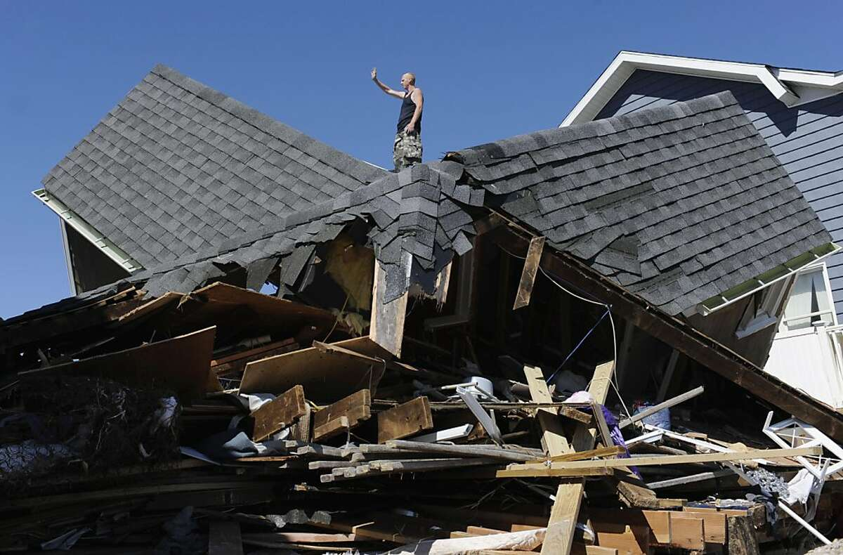 Tom Chase waves atop of his friend's beach home in the aftermath of Tropical Storm Irene, in East Haven, Conn., Monday, Aug. 29, 2011. (AP Photo/Jessica Hill)