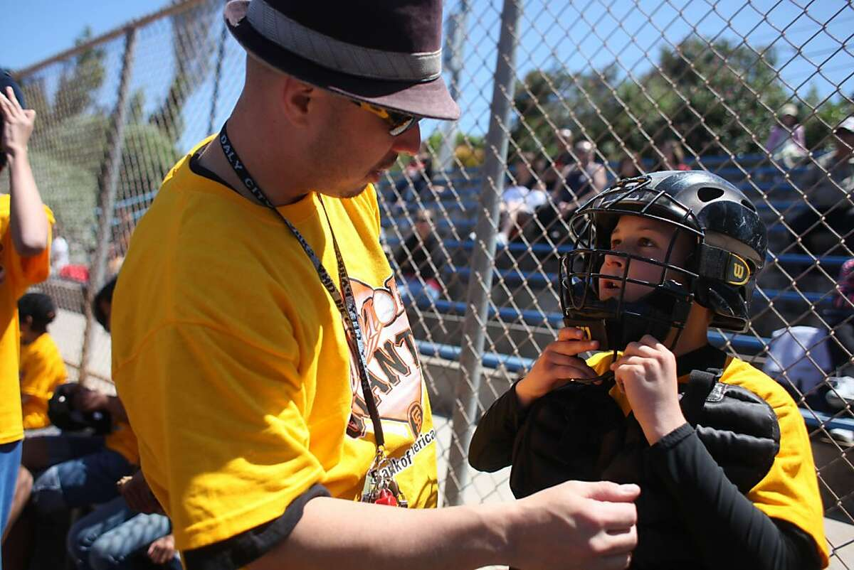 Chris Alcaraz (l to r), Junior Giants coach and Daly City Park and Recreation recreator, talks with Mario Repetto ,10 as he helps him get into his catchers gear during a Junior Giants baseball game at Westlake Park on Friday, July 1, 2011 in Daly City, Calif. The Giants Community Fund, which will be 20 years old this month, runs the Junior Giants.