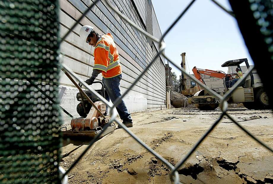 Porfirio Reyes runs a compacter, as the rebuilding of the Bayview Branch Library on the 5700 block of Third Street, in San Francisco, Ca., on Friday August 26, 2011, is well underway. The Library Commission decided last week to increase the project's budget from $11.8 million to $13.6 million, leading some to question whether the process' benefits outweigh the expense. Photo: Michael Macor, The Chronicle