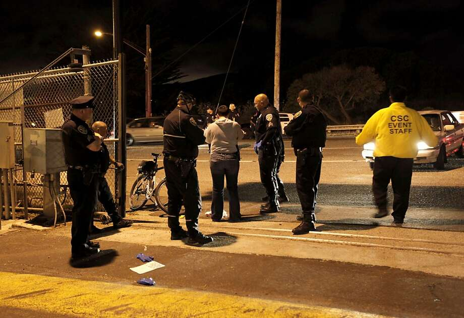 A police officers investigate the scene of a shooting just outside of lot L at Candlestick Park, where the San Francisco 49ers had just finished playing the Oakland Raiders  in San Francisco, Calif. on Saturday August 20, 2011. Photo: Michael Macor, The Chronicle