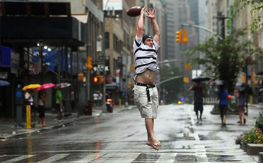 NEW YORK, NY - AUGUST 27:  Louis Leichtnam from Paris plays football barefoot on a deserted Broadway as Hurricane Irene approaches on August 27, 2011 in New York City. Approximately 370,000 city residents in low lying areas are under a mandatory evacuation order ahead of Hurricane Irene.  (Photo by Mario Tama/Getty Images) Photo: Mario Tama, Getty Images