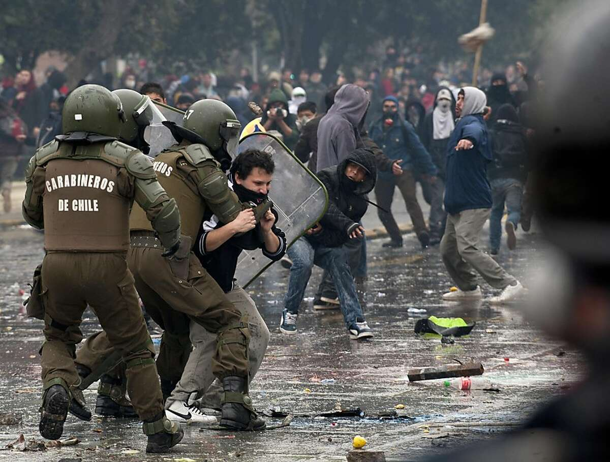 Riot police officers clash with protesting students in Santiago on August 25, 2011, during a 48-hour national strike - the first to hit Sebastian Pinera's government, convened by the largest workers union in the South American country with some 780,000 members. The reform protest, spurred by the education demands, will also include hospitals and emergency services, whose personnel are expected to only attend emergency shifts during the strike. Union officials also said taxi drivers and an association of truck drivers had joined the industrial action. Authorities said 42 police officers were injured and 108 protesters arrested during the night, a day after a series of clashes where 36 people were hurt and 348 arrested in the worst unrest of Sebastian Pinera's 17-month old presidency. AFP PHOTO/CLAUDIO SANTANA (Photo credit should read CLAUDIO SANTANA/AFP/Getty Images)