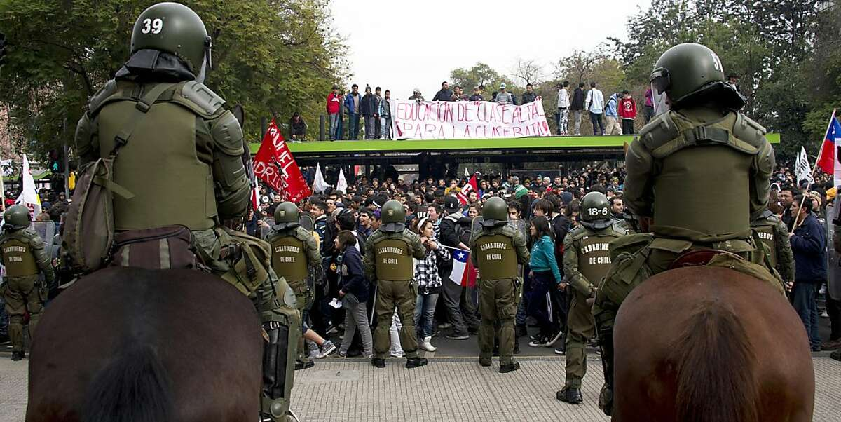 Riot police officers stand guard during protests in Santiago on August 25, 2011, during a 48-hour national strike - the first to hit Sebastian Pinera's government, convened by the largest workers union in the South American country with some 780,000 members. The reform protest, spurred by the education demands, will also include hospitals and emergency services, whose personnel are expected to only attend emergency shifts during the strike. Union officials also said taxi drivers and an association of truck drivers had joined the industrial action. Marches and rolling demonstrations by students demanding far-reaching education reforms and dismissing the government's latest plan to resolve the weeks-old crisis have continued for months now. AFP PHOTO/MARTIN BERNETTI (Photo credit should read MARTIN BERNETTI/AFP/Getty Images)