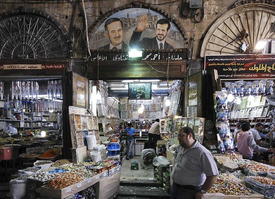A Syrian sweet vendor stands outside his shop with a picture above showing the late Syrian President Hafez Assad, left, and his dead son Bassel Assad, right, at a popular market in the old city of Damascus, Syria, on Monday Aug. 29, 2011. Syrian security forces pursuing anti-government protesters stormed a northern village Monday, killing at least one person and wounding many others during raids and house-to-house searches, activists said. Syria has come under blistering international condemnation for its deadly crackdown on anti-government protests that began in March, and U.S. and European leaders have demanded Assad step down. (AP Photo/Muzaffar Salman) Photo: Muzaffar Salman, AP
