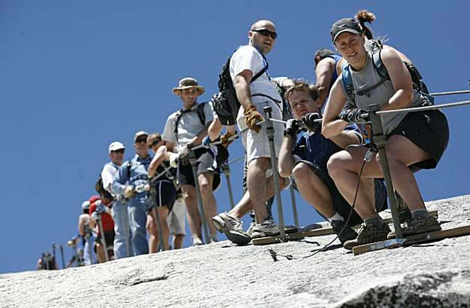 Climbers on the cable section of Half Dome descend the steep granite pitch, some holding on for dear life, others without any concern whatsoever. The weekend summer crowds climbing Half Dome in Yosemite National Park have raised safety concerns among the climbers and park. Hundreds climb the precarious cable section every summer weekend day - many who are not prepared for the strenuous hike and 100 yard cable climb. Photos taken at Half Dome on Saturday, June 30, 2007. Photo by Michael Maloney / San Francisco Chronicle  *** Ran on: 11-04-2007 Yosemite ranger Jesse McGahey inspects a rope abandoned at the base of El Capitan, emblematic of the gear and trash left behind by novices unschooled in climbing ethics.  Ran on: 02-10-2010 Climbers in 2007 line up on Half Dome's cable section, waiting to make the steep descent. New required permits will be available starting March 1. Ran on: 02-10-2010 Climbers in 2007 line up on Half Dome's cable section, waiting to make the steep descent. Newly required permits will be available starting March 1. Photo: Michael Maloney, The Chronicle