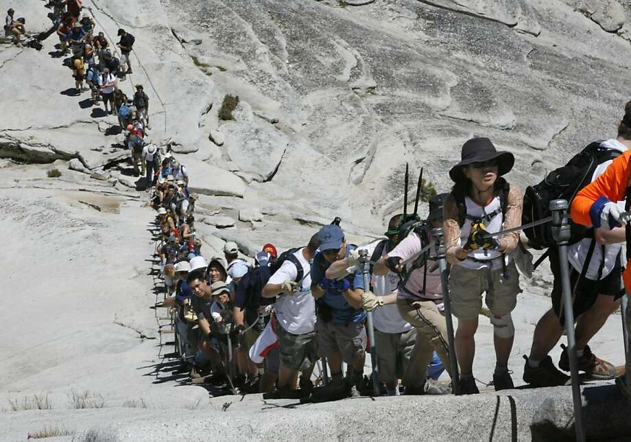 The late afternoon weekend crowd on the cable section of Half Dome. The weekend summer crowds climbing Half Dome in Yosemite National Park have raised safety concerns among the climbers and park. Hundreds climb the precarious cable section every summer weekend day - many who are not prepared for the strenuous hike and 100 yard cable climb. Photos taken at Half Dome on Saturday, June 30, 2007. Photo by Michael Maloney / San Francisco Chronicle  ***   Ran on: 03-06-2011 The mass of people trying to negotiate the Half Dome cable route in Yosemite National Park began to threaten safety and has resulted in a quota system. Now, reservations are snatched up in minutes online. Ran on: 03-06-2011 The mass of people trying to negotiate the Half Dome cable route in Yosemite National Park began to threaten safety and has resulted in a quota system. Photo: Michael Maloney, The Chronicle