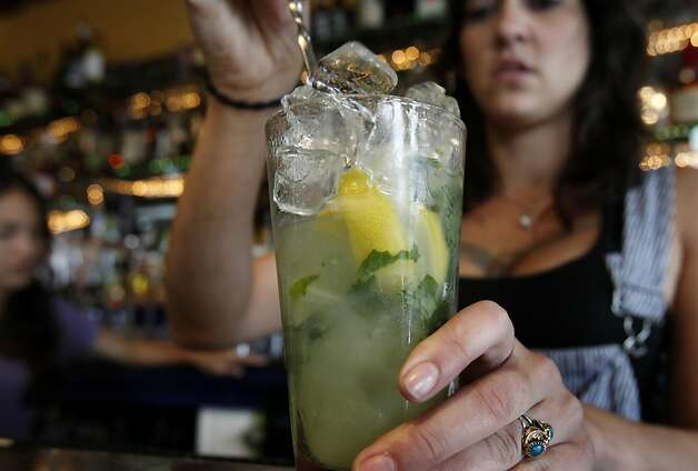 Bartender Amber Triolo mixes alcohol into her concoction of mint, ginger and lemon. At Mars Bar and Restaurant in San Francisco, Calif. bartender Amber Triolo makes her drinks fresh, but would like to infuse alcohol if it becomes legal in the state. The California State legislature is debating a new measure which would allow bars to legally infuse alcohol with fruit and herbs. Photo: Brant Ward, The Chronicle