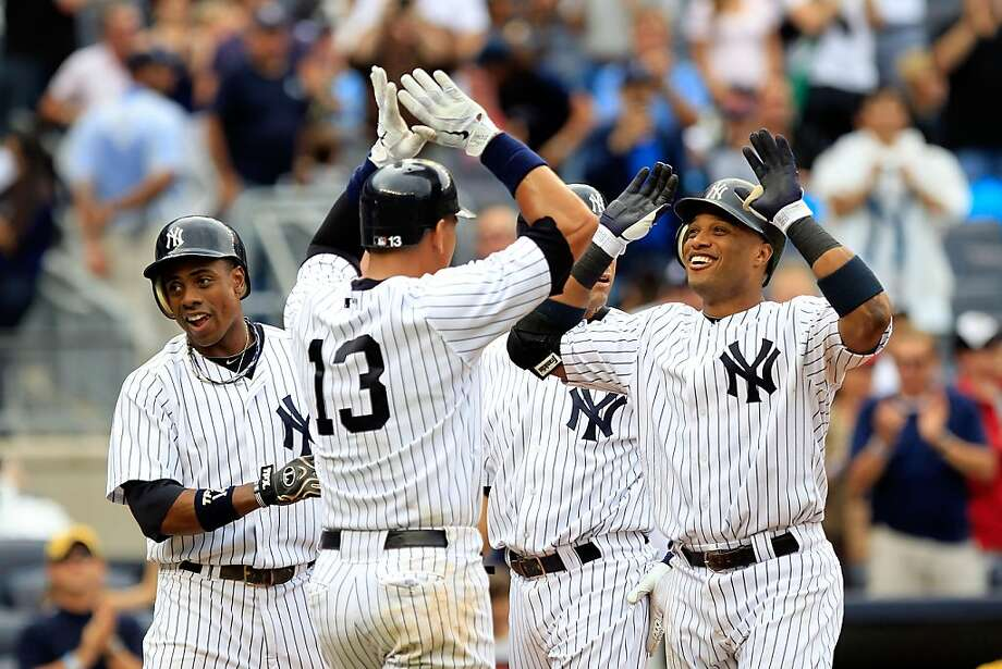 NEW YORK, NY - AUGUST 25:  Robinson Cano #24 of the New York Yankees is congratulated by his teammates Curtis Granderson, Alex Rodriguez #13 and Derek Jeter for his grand slam home run in the 5th inning against the Oakland Athletics on August 25, 2011 at Yankee Stadium in the Bronx borough of New York City.  (Photo by Chris Trotman/Getty Images) Photo: Chris Trotman, Getty Images