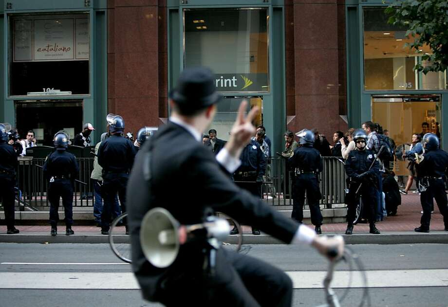 A protestor on a bike flashes the peace sign to police surrounding the entrance to the BART station during a BART protest in San Francisco, Calif., Monday, August 29, 2011.  Protestors marched from the Civic Center BART station down to the Embarcadero station, stopping in each along the way, before disbanding. Photo: Sarah Rice, Special To The Chronicle