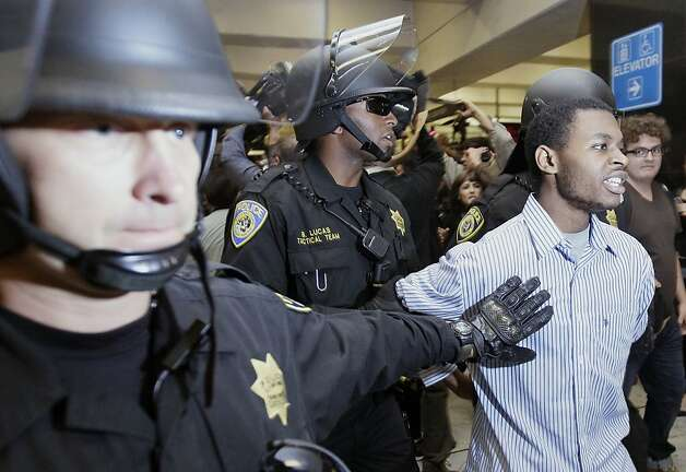 Bay Area Rapid Transit (BART) police officers arrest a man during a protest at the Civic Center train station in San Francisco, Monday, Aug. 22, 2011. The small demonstration involving about two dozen protesters prompted BART officials to close the Civic Center station at 5:30 p.m. Demonstrators and computer hackers have been targeting BART for shutting down wireless service at Civic Center on Aug, 11 to quell a brewing protest over a shooting by transit police. (AP Photo/Jeff Chiu) Photo: Jeff Chiu, AP