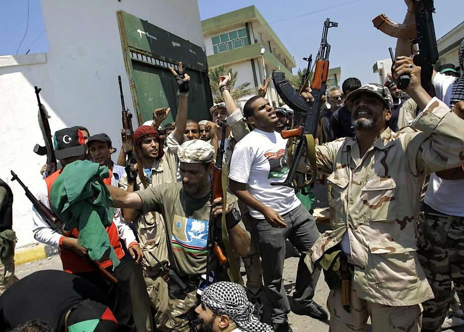 Libyan rebel fighters gesture at the former female military base in Tripoli, LIbya, Monday, Aug. 22, 2011. Libyan rebels claimed to be in control of most of the Libyan capital on Monday after their lightning advance on Tripoli heralded the fall of Moammar Gadhafi's nearly 42-year regime, but scattered battles erupted and the mercurial leader's whereabouts remained unknown. (AP Photo/Sergey Ponomarev) Ran on: 08-23-2011 Insurgents celebrate a day after their victorious march into Tripoli, where fighting reportedly continues. Photo: Sergey Ponomarev, AP