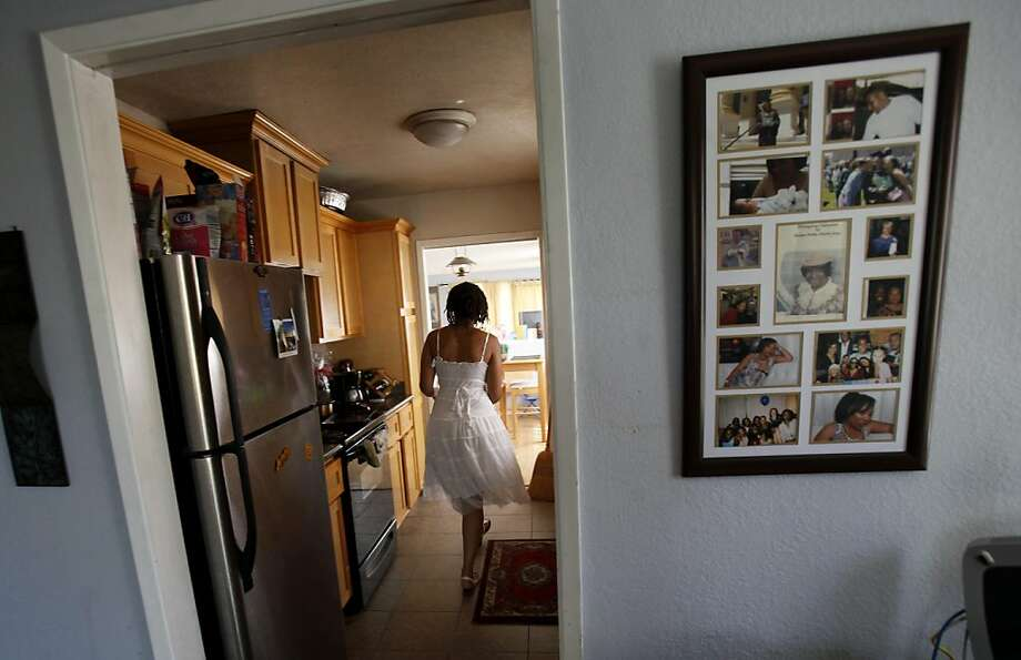 With family pictures on the wall, Oya Sherrills walks through her home in El Sobrante. Oya Sherrills, 23, lost her brother to gang violence in 2004 but she still supports SB9, which would let juvenile offenders appeal their life without parole sentences. Photo: Brant Ward, The Chronicle