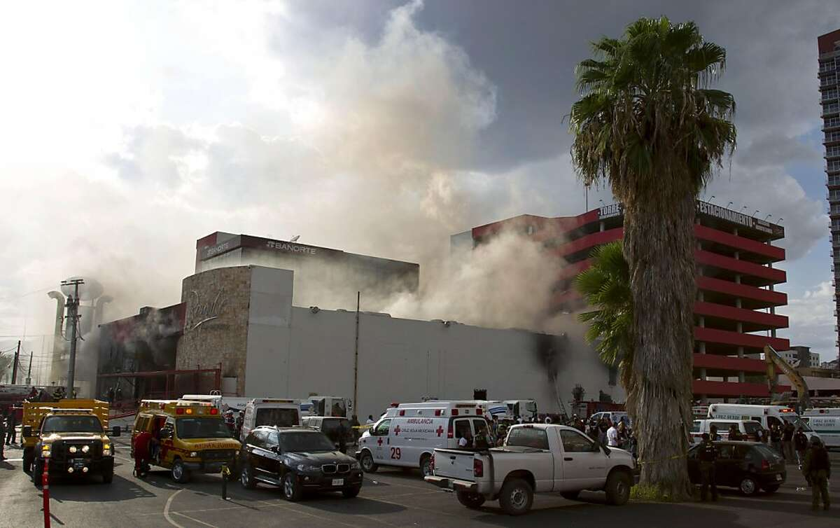 Smoke billows from the Casino Royale as rescue vehicles surround the building in Monterrey, Mexico, Thursday Aug. 25 2011. Two dozen gunmen burst into the casino in northern Mexico on Thursday, doused it with a flammable liquid and started a fire that trapped gamblers inside, killing at least 32 people and injuring a dozen more, authorities said. (AP Photo/Hans Maximo Musielik)