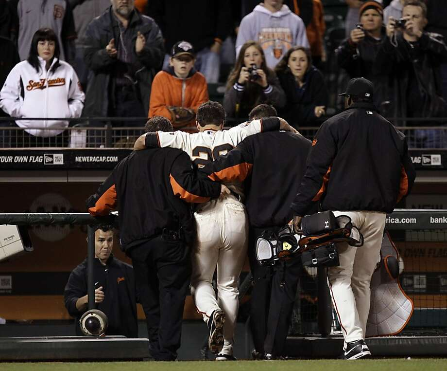 San Francisco Giants catcher Buster Posey (28) is carried off the field after a collision with Florida Marlins' Scott Cousins during the 12th inning of a baseball game in San Francisco, Wednesday, May 25, 2011.  Cousins scored the go-ahead run on the play as Florida won 7-6. (AP Photo/Marcio Jose Sanchez) Ran on: 05-28-2011 Buster Posey is helped off the field after baserunner Scott Cousins ran into him Wednesday at AT&T Park. Photo: Marcio Jose Sanchez, AP