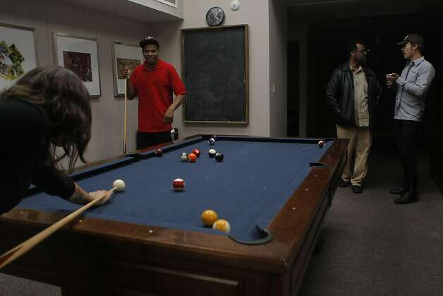 John Chatman plays pool with Jessica Burleigh, one of the Larkin Youth Services group home staff members while the program manager Carlton Benson speaks with another staff member at the Larkin Street Youth Services home in San Francisco Calif.,  on August 19, 2011. Photo: Audrey Whitmeyer-Weathers, The Chronicle