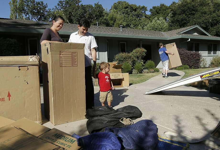 Arian Brackett and Dr. Steve LeVine with their son Ezra, as their belongings are moved into their new home on Tuesday August 23, 2011,  in Moraga, Ca. They were able to lock in their mortgage rate before the change in limits goes into effect at the end of next month, which would have made their new home more expensive. Photo: Michael Macor, The Chronicle