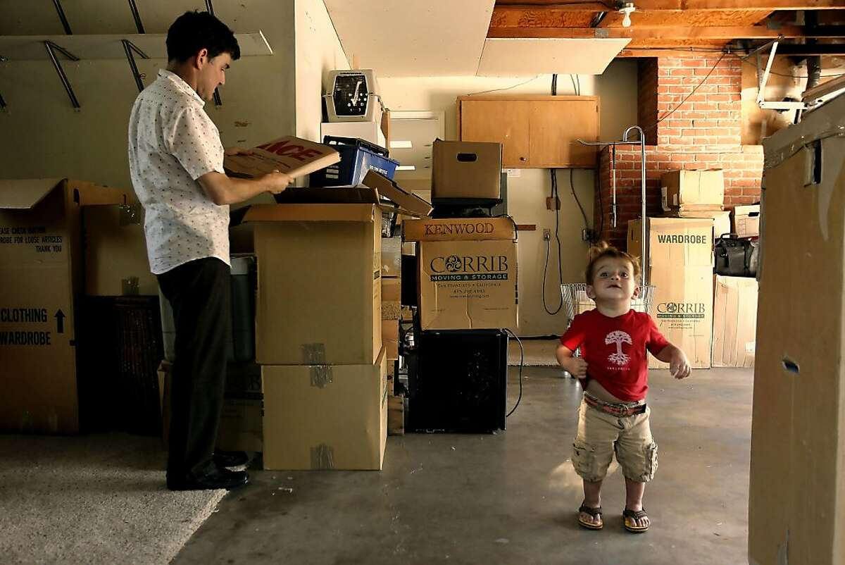 Dr. Steve LeVine unpacks boxes in his new garage with his son Ezra close by. LeVine and his wife Arian Brackett are moving into their new home on Tuesday August 23, 2011, in Moraga, Ca. They were able to lock in their mortgage rate before the change in limits goes into effect at the end of next month, which would have made their new home more expensive.
