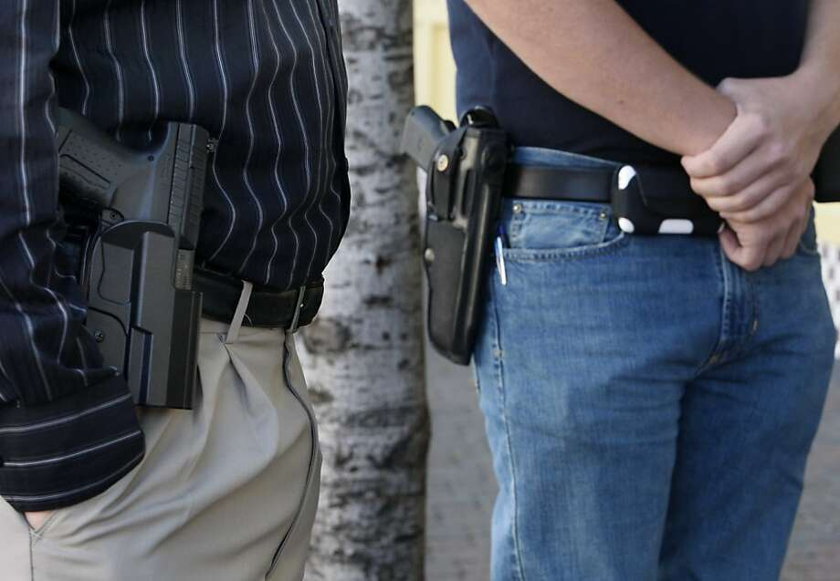 """Jeff Dunhill (left) and Brad Huffman wear their sidearms while walking in downtown Walnut Creek, Calif., on Wednesday, April 7, 2010. Dunhill and Huffman are among a growing number of gun owners that are advocating the """"Open Carry"""" law which allows law abiding citizens to carry holstered unloaded handguns.  Ran on: 04-21-2010 Members of the &quo;open carry&quo; movement, advocating the right to carry unloaded weapons in public, stroll through downtown Walnut Creek.  Ran on: 05-19-2010 Jeff Dunhill (left) and Brad Huffman wear their sidearms in downtown Walnut Creek last month. California's &quo;open carry&quo; movement is threatened by a bill introduced in the Assembly. Photo: Paul Chinn, The Chronicle"""