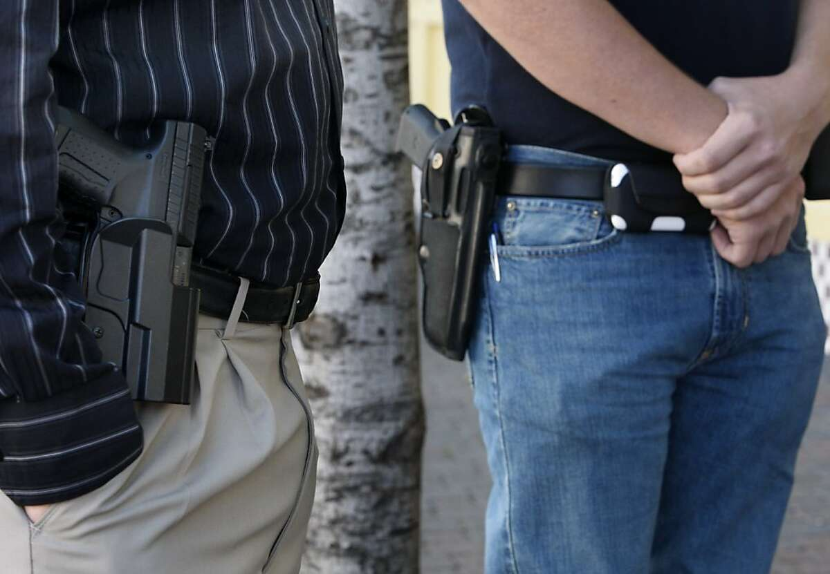 """Jeff Dunhill (left) and Brad Huffman wear their sidearms while walking in downtown Walnut Creek, Calif., on Wednesday, April 7, 2010. Dunhill and Huffman are among a growing number of gun owners that are advocating the """"Open Carry"""" law which allows law abiding citizens to carry holstered unloaded handguns. Ran on: 04-21-2010 Members of the open carry movement, advocating the right to carry unloaded weapons in public, stroll through downtown Walnut Creek. Ran on: 05-19-2010 Jeff Dunhill (left) and Brad Huffman wear their sidearms in downtown Walnut Creek last month. Californias open carry movement is threatened by a bill introduced in the Assembly."""
