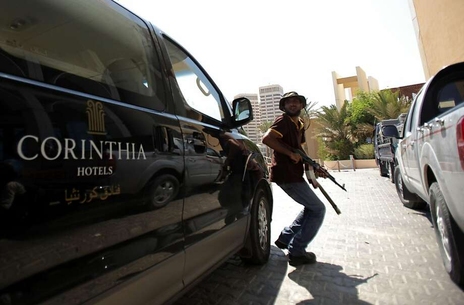 A Libyan rebel takes cover as Tripoli's central Corinthia Bab Africa Hotel, where numerous foreign journalists are based, came under attack on August 25, 2011. AFP PHOTO/PATRICK BAZ (Photo credit should read PATRICK BAZ/AFP/Getty Images) Photo: Patrick Baz, AFP/Getty Images
