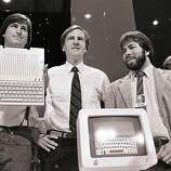 In this April 24, 1984 file photo, Steve Jobs, left, chairman of Apple Computers, John Sculley, center, then president and CEO, and Steve Wozniak, co-founder of Apple, unveil the new Apple IIc computer in San Francisco. Apple Inc. on Wednesday, Aug. 24, 2011 said Jobs is resigning as CEO, effective immediately. He will be replaced by Tim Cook, who was the company's chief operating officer. It said Jobs has been elected as Apple's chairman.