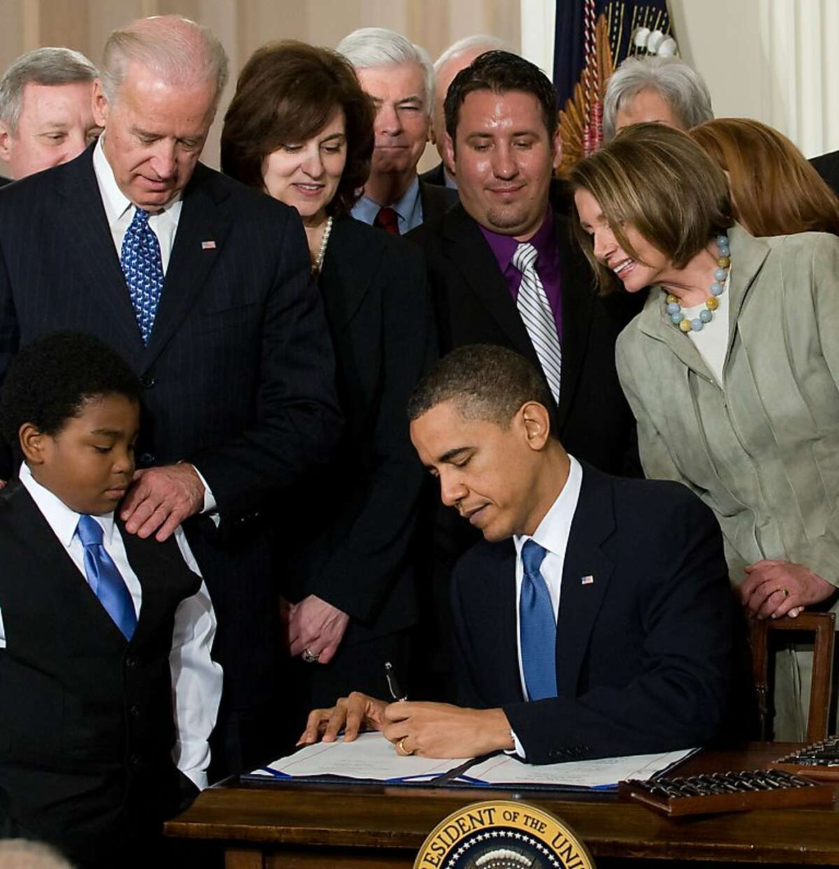 US President Barack Obama, surrounded by lawmakers and guests, signs the healthcare insurance reform legislation during a ceremony in the East Room of the White House in Washington on March 23, 2010. Obama signed into law his historic health care reform, enacting the most sweeping social legislation in decades which will ensure coverage for almost all Americans. AFP PHOTO / Saul LOEB (Photo credit should read SAUL LOEB/AFP/Getty Images) Ran on: 03-24-2010 President Obama signs the health care overhaul bill surrounded by officials, guests and Marcelas Owens, 11, of Seattle, who began campaigning for the bill after his uninsured mother died of pulmonary hypertension. Ran on: 03-24-2010 President Obama signs the health care overhaul bill surrounded by officials, guests and Marcelas Owens, 11, of Seattle, who began campaigning for the bill after his uninsured mother died of pulmonary hypertension. Ran on: 04-04-2010 President Obama signs the health care insurance reform bill in the East Room of the White House. At left is Marcelas Owens, 11, of Seattle, who began campaigning for the bill after his uninsured mother died of hypertension. Ran on: 04-04-2010 President Obama signs the health care insurance reform bill in the East Room of the White House. At left is Marcelas Owens, 11, of Seattle, who began campaigning for the bill after his uninsured mother died of hypertension. Ran on: 12-26-2010 President Obama and House Speaker Nancy Pelsoi passed health care reform, but paid for it in the November election. Ran on: 12-26-2010 President Obama and House Speaker Nancy Pelsoi passed health care reform, but paid for it in the November election. Ran on: 03-20-2011 President Obama signed the health care overhaul legislation last March. The bills proponents said it would increase access to the system for...