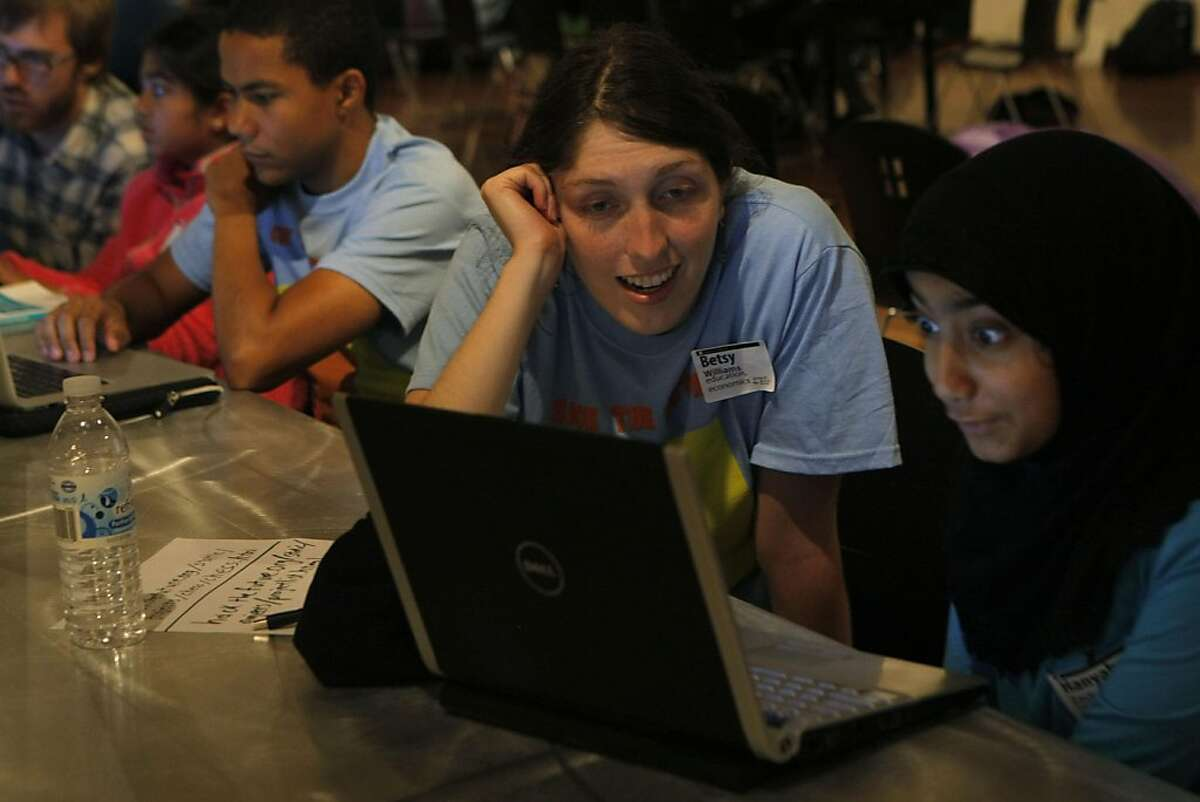 """Betsy Williams helps Hanyah Zachnah as she learns to hack a game of chess at the """"Hack the Future"""" event at the Tech Museum in San Jose Calif., on August 20, 2011."""