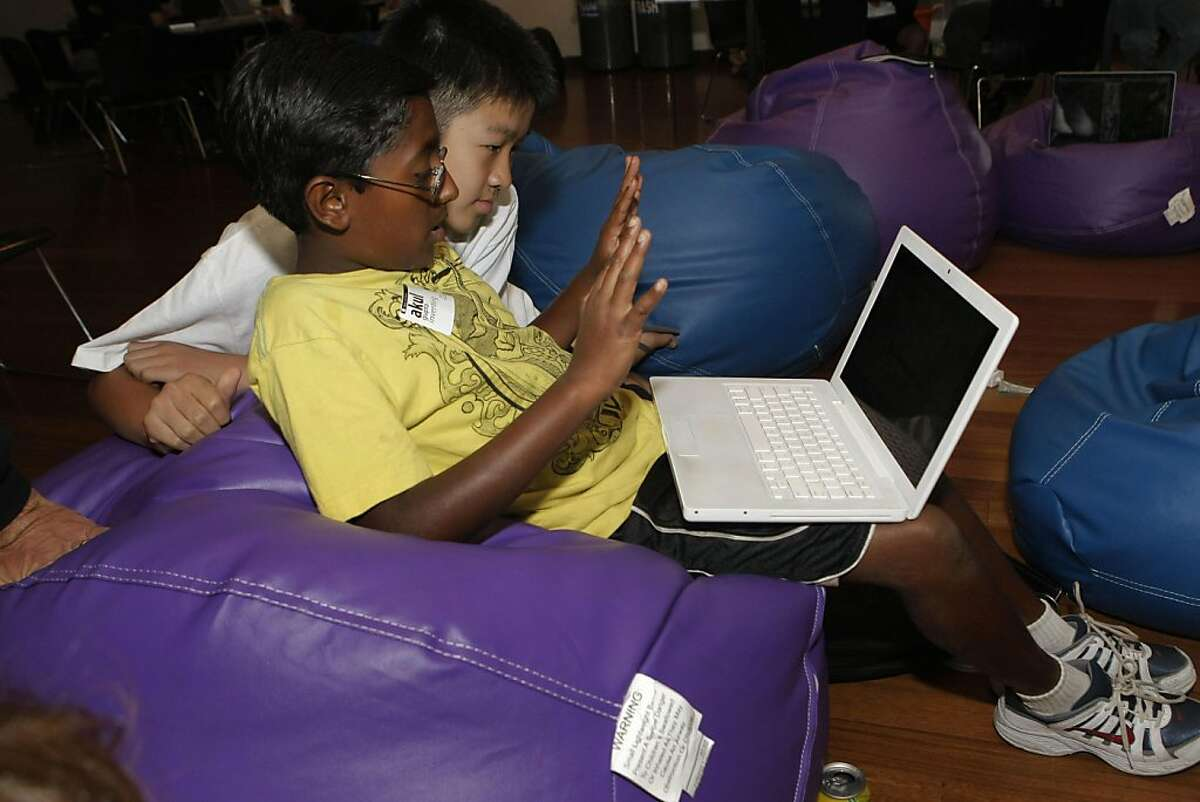 """Akul Gupta and Cary Xiao work at the Robot Workshop section where kids get to use programs that make a robot do things like give a hugh or a high five at the """"Hack the Future"""" event at the Tech Museum in San Jose Calif., on August 20, 2011."""