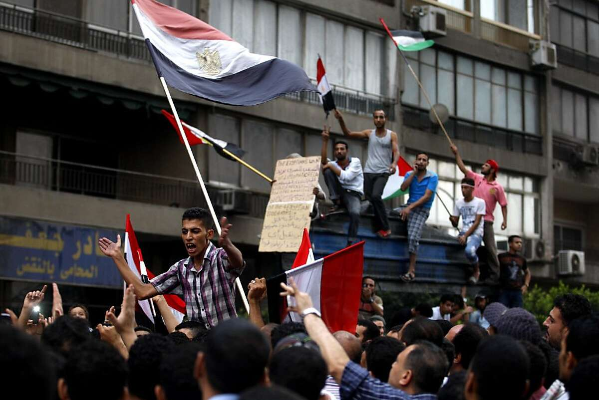 Egyptians chant anti-Israeli slogans and hold Egyptian and Palestinian flags as they protest the deaths of Egyptian security forces killed in a shootout between Israeli soldiers and Palestinian militants on Thursday in the Sinai, in front of the Israeli embassy in Cairo, Egypt, Saturday, Aug. 20, 2011. Egypt said Saturday it would recall its ambassador from Israel to protest the deaths, sharply escalating tensions between the neighboring countries, whose 1979 peace treaty is being tested by the fall of Egypt's longtime autocratic leader, Hosni Mubarak. (AP Photo/Khalil Hamra)