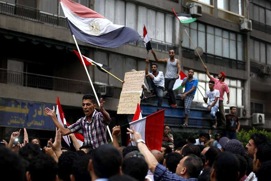 Egyptians chant anti-Israeli slogans and hold Egyptian and Palestinian flags as they protest the deaths of Egyptian security forces killed in a shootout between Israeli soldiers and Palestinian militants on Thursday in the Sinai, in front of the Israeli embassy in Cairo, Egypt, Saturday, Aug. 20, 2011. Egypt said Saturday it would recall its ambassador from Israel to protest the deaths, sharply escalating tensions between the neighboring countries, whose 1979 peace treaty is being tested by the fall of Egypt's longtime autocratic leader, Hosni Mubarak. (AP Photo/Khalil Hamra) Photo: Khalil Hamra, AP