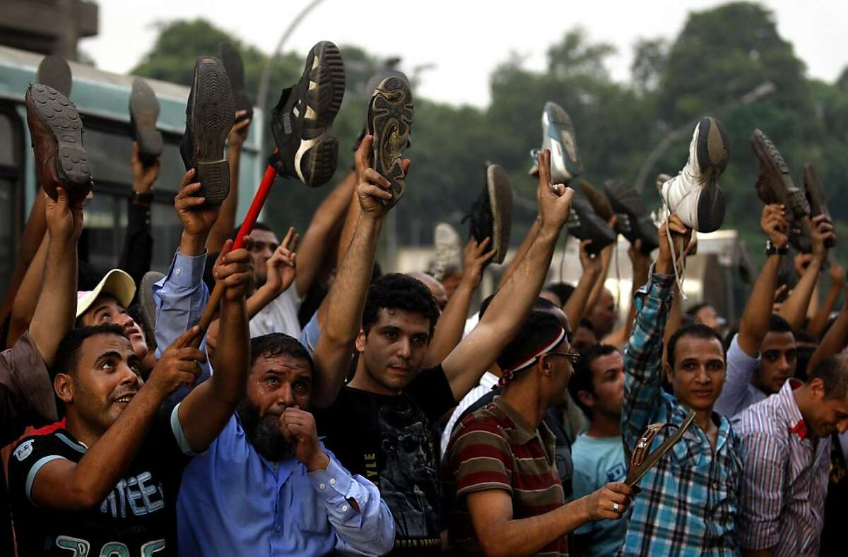 Egyptians hold their shoes up to protest the deaths of Egyptian security forces killed in a shootout between Israeli soldiers and Palestinian militants on Thursday in the Sinai, in front of the Israeli embassy in Cairo, Egypt, Saturday, Aug. 20, 2011. Egypt said Saturday it would recall its ambassador from Israel to protest the deaths, sharply escalating tensions between the neighboring countries, whose 1979 peace treaty is being tested by the fall of Egypt's longtime autocratic leader, Hosni Mubarak. (AP Photo/Khalil Hamra)