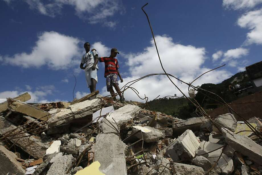 In this Tuesday July 26, 2011 photo, Julio Cesar, 18, left, and friend Vitor, 14, stand on the debris of Cesar's house, destroyed by a January mudslide, in Teresopolis, Brazil. The natural disaster that struck the mountainous town north of Rio de Janeiro was the worst to hit Brazil in a century: 918 people died; 322 were never found and are presumed dead. Now, residents are hit with another catastrophe. Elected officials are accused of graft and corruption in handling the funds meant to restore the lives of the tens of thousands who lost everything. (AP Photo/Silvia Izquierdo)  Ran on: 08-21-2011 Young men stand atop the wreckage of a house in Teresopolis last month destroyed by the avalanche. Photo: Silvia Izquierdo, AP