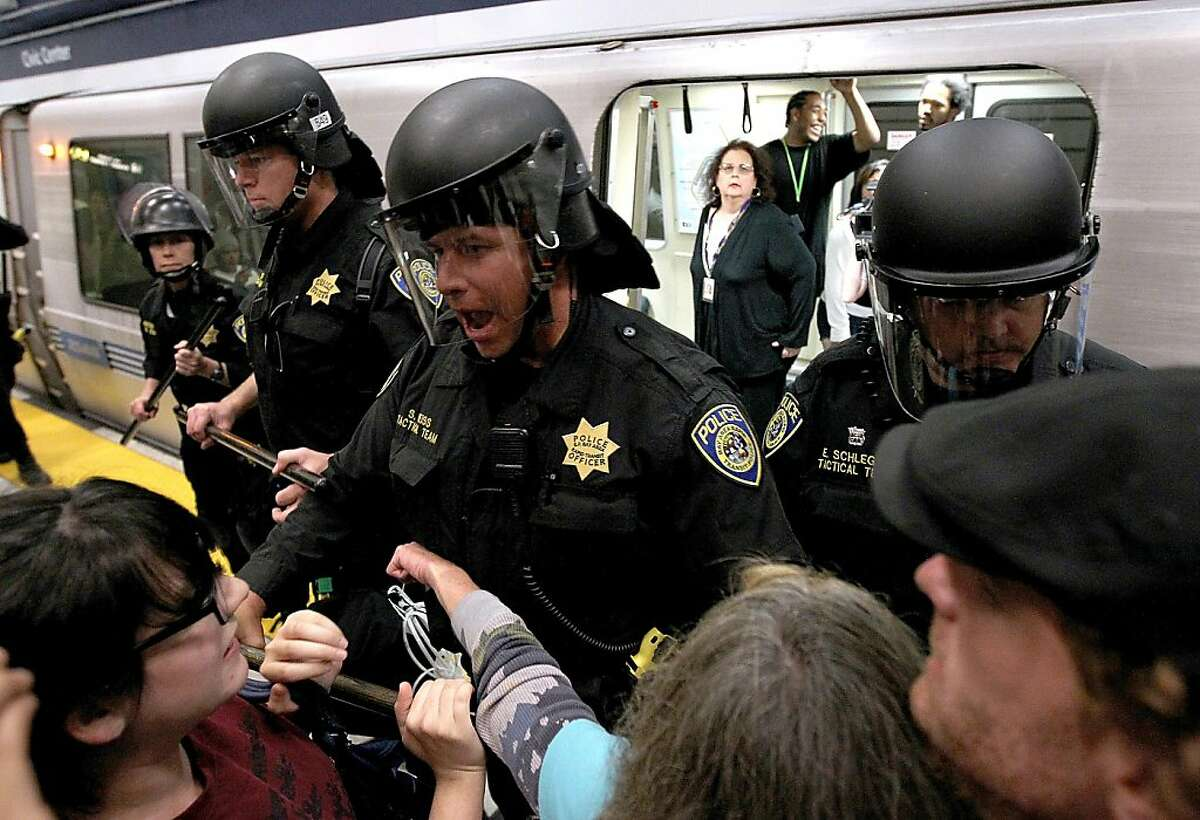 SAN FRANCISCO, CA - AUGUST 15: Bay Area Rapid Transit (BART) police push back demonstrators that are trying to keep a train from leaving the Civic Center station on August 15, 2011 in San Francisco, California. The hacker group