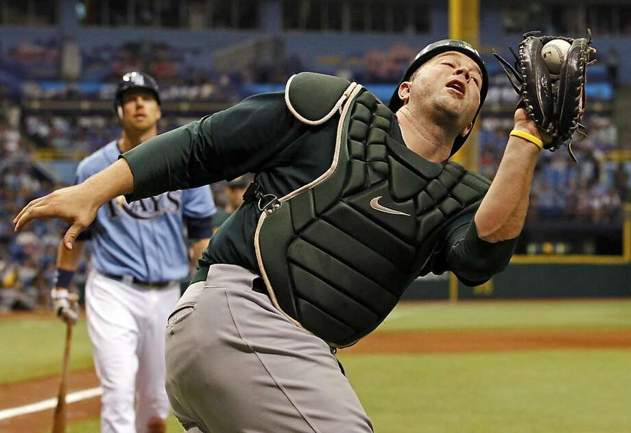 Oakland Athletics catcher Landon Powell, foreground, catches a foul ball hit by Tampa Bay Rays' Ben Zobrist during the seventh inning of a baseball game  onSunday, Aug. 7, 2011, in St. Petersburg, Fla. During the at-bat Zobrist, hit a double which was overruled on an umpire appeal of a fair/foul ball. (AP Photo/Mike Carlson) Photo: Mike Carlson, AP